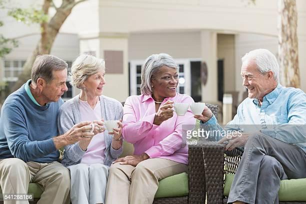 Rassen leitender Freunde trinken Kaffee im Freien