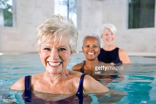 Multirracial mujeres mayores en la piscina bajo techo, gimnasio y spa