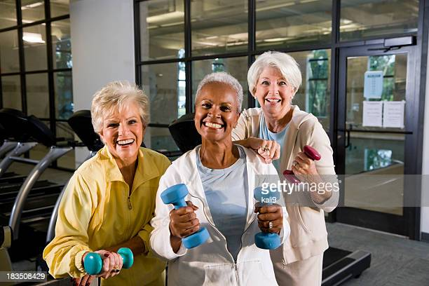 Multiracial senior women staying fit in the gym lifting handweig