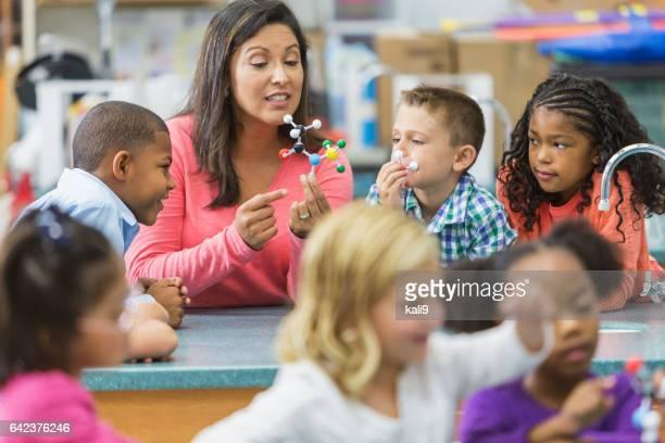 Multiraciale leraar en kinderen in science lab