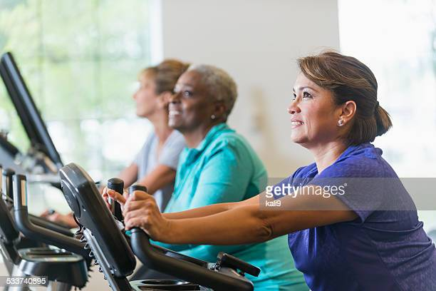 Multiracial women riding exercise bikes at gym