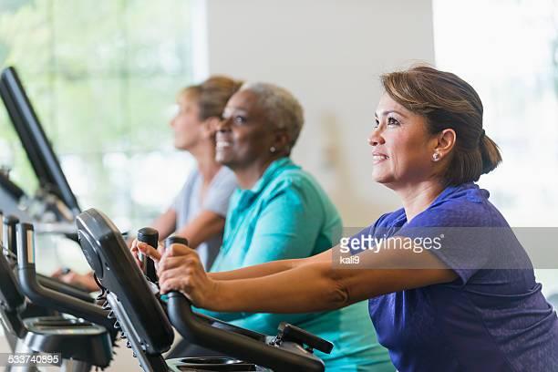 Multiraciale femmes équitation vélos d'exercice dans la salle de sport