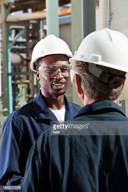 Multiracial workers at industrial plant talking
