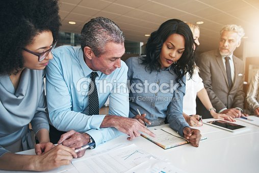 Multiracial workers discussing papers sitting in office : Stock Photo