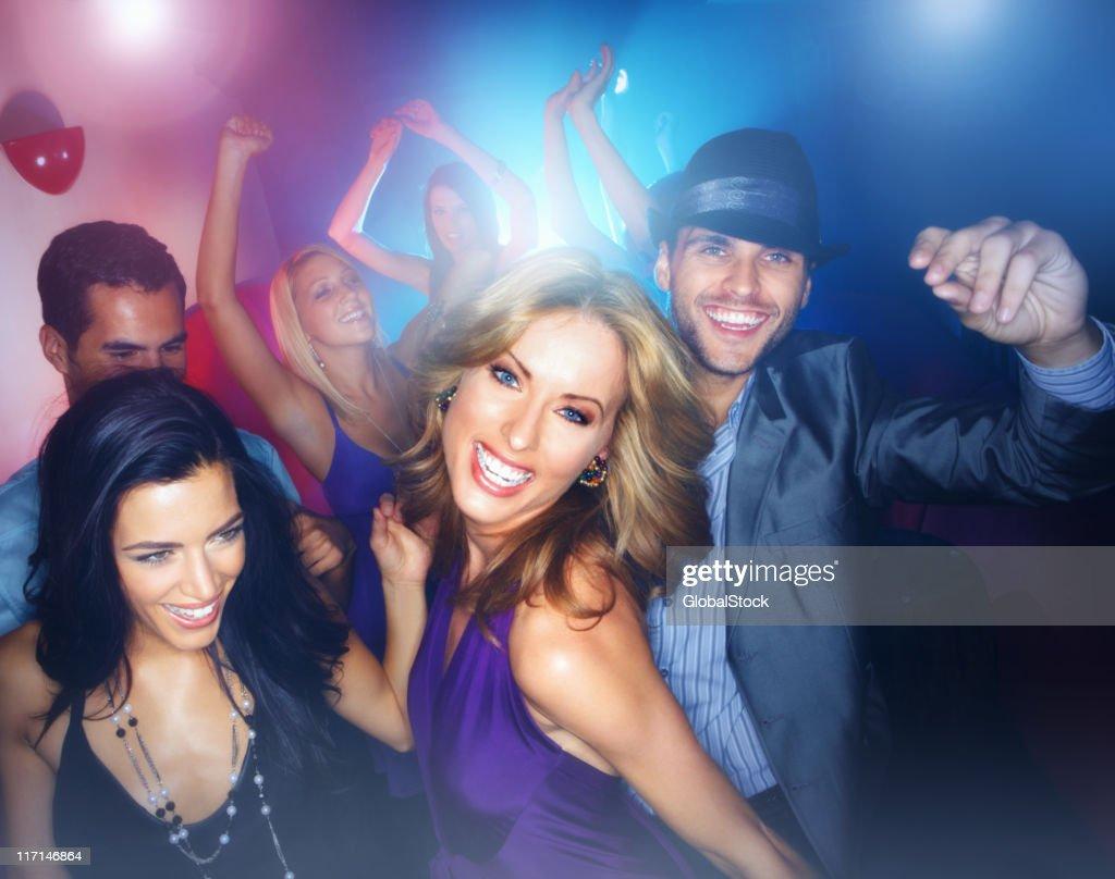 Multiracial young boys and girls enjoying in a nightclub : Stock Photo