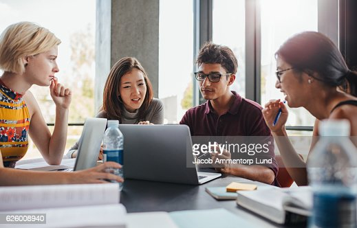 Multiracial young people doing group study at library : Stock Photo