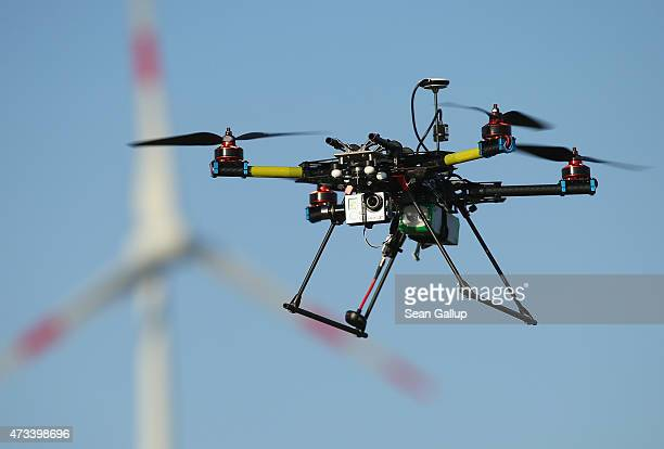 A multirotor quadcopter drone used for aerial photography flies near a wind turbine on June 7 2011 near Zeestow Germany Many governments in Europe...