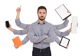 Confident man with office supplies in six hands, white background