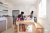 Mum and dad help their kids with homework at kitchen table