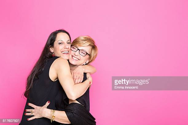 mum and daughter hugging on pink background