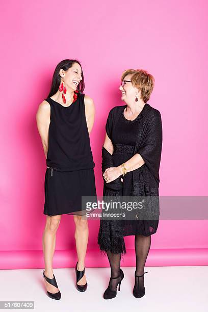 mum and daughter in black dress on pink background