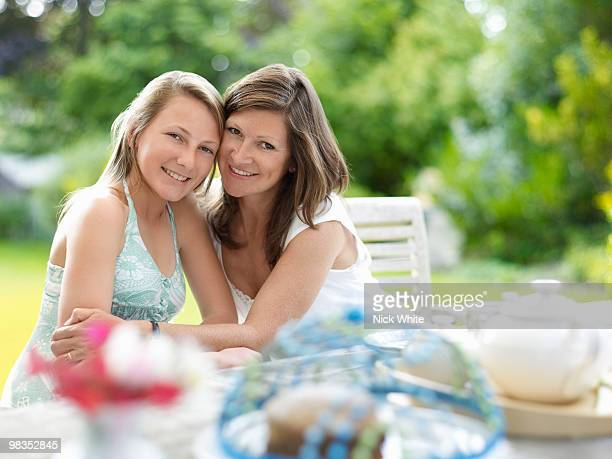 mum and daughter take tea in garden