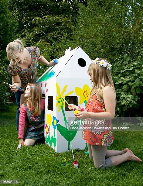 Mum and girls play with wendy house