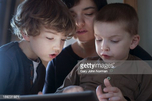 mum and two boys look at digital tablet : Stock Photo