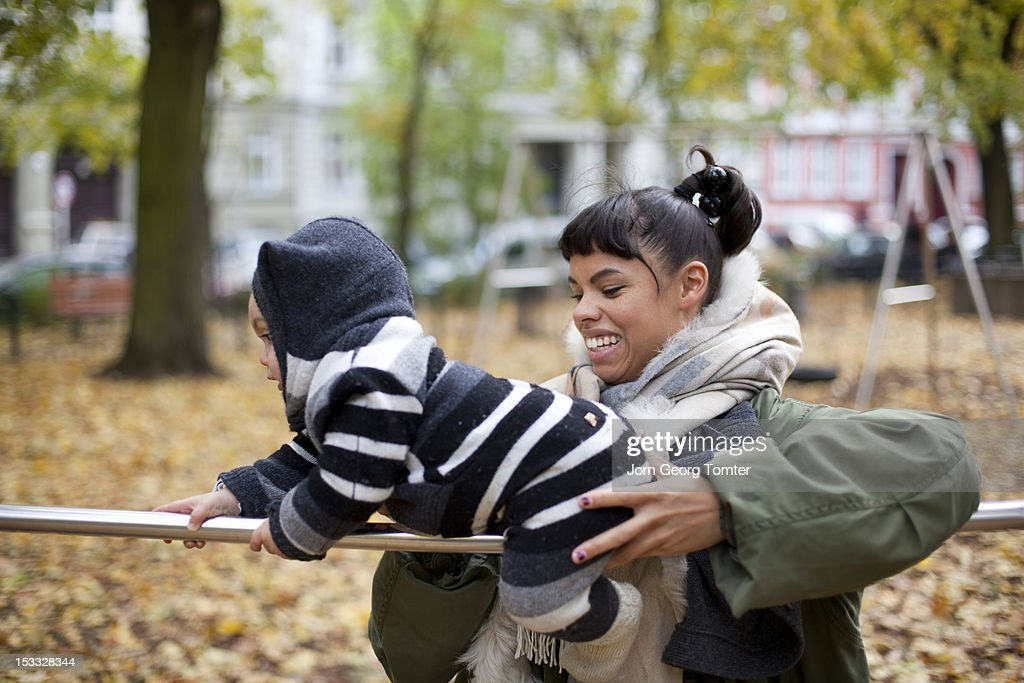 Mum helping her baby to balance on a metal bar : Stock Photo