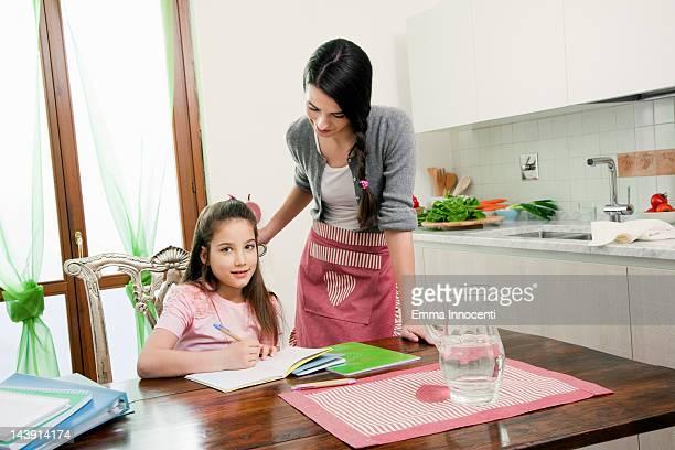mum looking at children doing homework