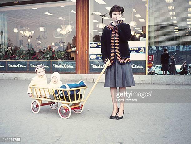 Mum pulling daughters in cart