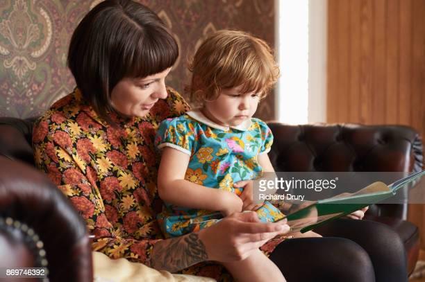 Mum reading book to toddler daughter