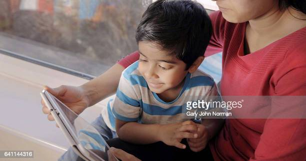 Mum reading book to young son.