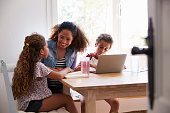 Mum sitting with kids at kitchen table, son using laptop