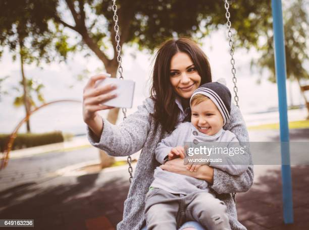 Mum taking a selfie with her son on a swing