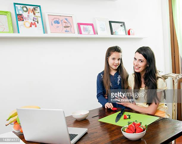 mum with daughter, kitchen table, laptop, fruit
