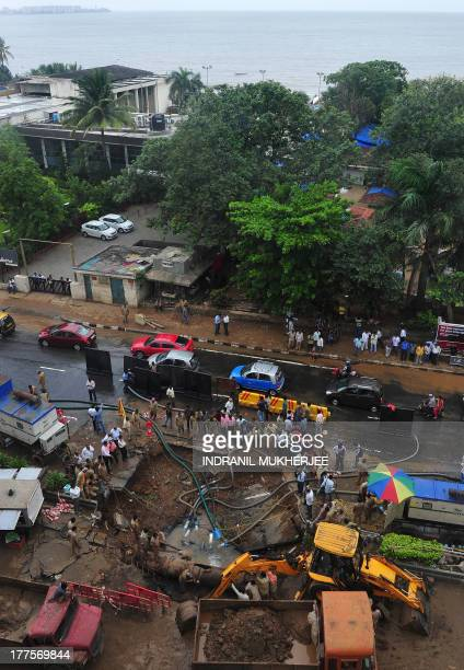 Mumbai City civic staff work to repair a burst underground pipeline which resulted in the cavein of a portion of the city's Marine Drive dubbed the...