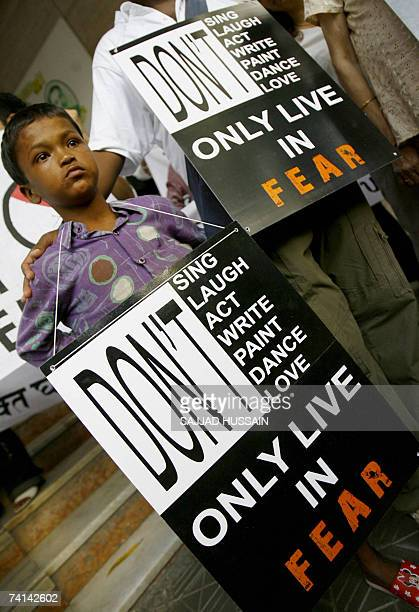 An Indian child holds a placard as he takes part in a protests alongside local artists outside a prestigious art gallery in Mumbai 14 May 2007...