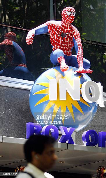 An Indian movie goer walks under a Spiderman action figure displayed at the INOX Multiplex in Mumbai 05 May 2007 'Spiderman 3' opened across India's...