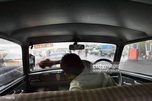 An Indian taxi driver wipes the moisture off the inside of his windscreen during a heavy downpour in Mumbai31 May 2006 With heavy rains lashing the...