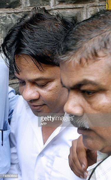 Fugitive gangster Dawood Ibrahim's brother Iqbal Kaskar is escorted by a policeman as he leaves the Arthur Road jail in Mumbai 14 June 2007 Kaskar...