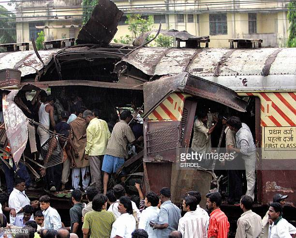In this file photo taken 11 July 2006 Rescue workers search for bodies inside the mangled compartment of one of the blast affected local trains at...