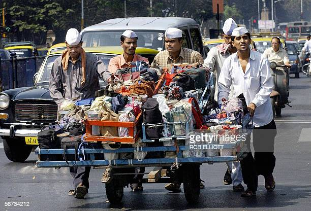 In this picture taken 04 February 2004 Indian dabbawallahs or tiffin carriers push their cart laden with food on their way to make lunch time food...