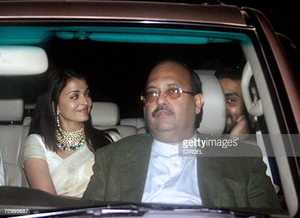 Indian film actress Aishwarya Rai and actor Abhishek Bachchan sit inside a car alongwith Bachchan family friend and poltician Amar Singh as they...