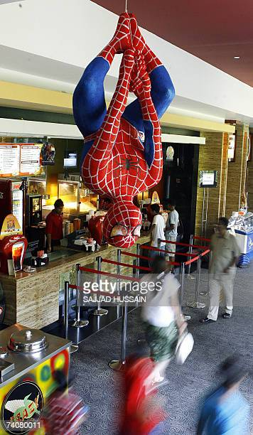 Indian movie goers walk under a Spiderman action figure displayed at the INOX Multiplex in Mumbai 05 May 2007 'Spiderman 3' opened across India's...