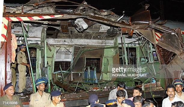 Police and onlookers stand around a mangled commuter train's wagon following a series of blasts which targetted India's financial capital commuters'...