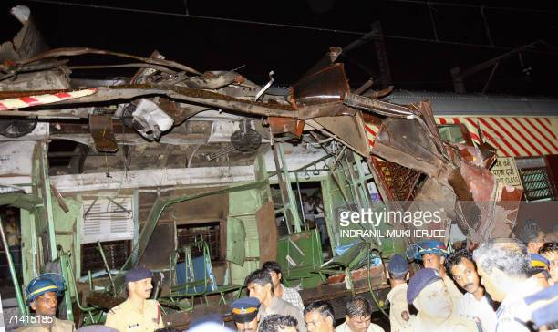 Police and onlookers stand around the mangled compartment of one of the bombed trains in Mumbai 11 July 2006 Several blasts in trainss rocked the...