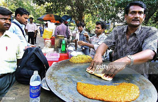 TO GO WITH INDIAECONOMYHAWKERS In this picture taken 07 April 2006 Indian hawker Feroze Chowdhary prepares paobhaji a snack of bread and curry for...