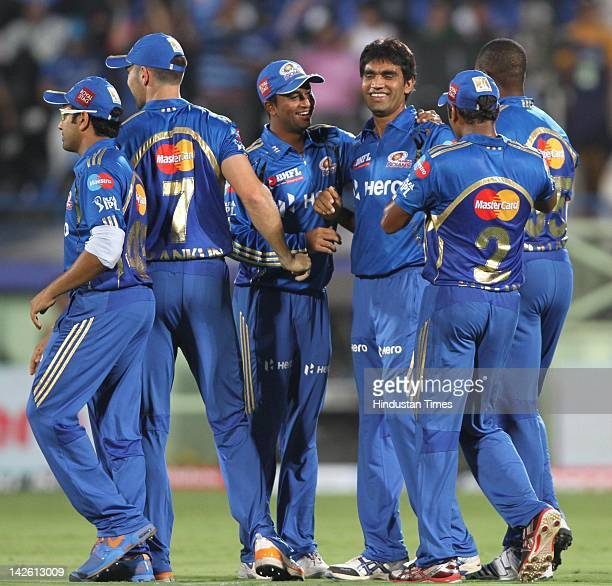 Mumbai Indian bowler Munaf Patel celebrates with teammates after taking the wicket of Deccan Chargers batsman Bharat Chipli during IPL5 cricket match...