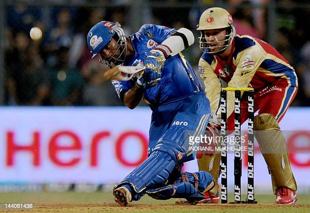 Mumbai Indians batsman Dinesh Karthik plays a shot as Royal Challengers bangalore wicket keeper AB De Villiers looks on during the IPL Twenty20...