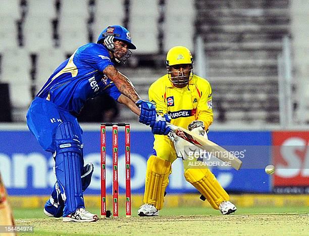 Mumbai Indians batsman Mitchell Johnson swings at the last ball as Chennal Super Kings wicketkeeper Mahendra Singh Dhoni waits to make a catch on...