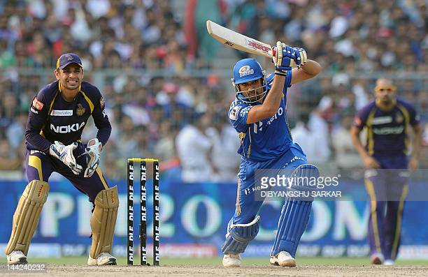 Mumbai Indians batsman Rohit Sharma is watched by Kolkata Knight Riders wicketkeeper Manvinder Bisla as he plays a shot during the IPL Twenty20...