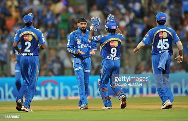 Mumbai Indians bowler Harbhajan Singh celebrates with his teammates after he dismissed Delhi Daredevils batsman David Warner during the IPL Twenty20...
