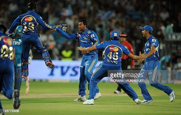 Mumbai Indians bowler Pragyan Ojha celebrates with teammates after taking the wicket of unseen Pune Warriors India batsman Steve Smith during the IPL...