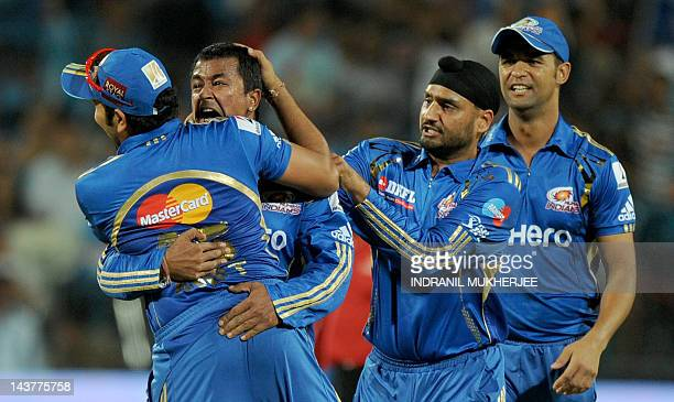 Mumbai Indians' bowler Pragyan Ojha is congratulated by his teammates after taking the wicket of unseen Pune Warriors India's batsman Steve Smith...