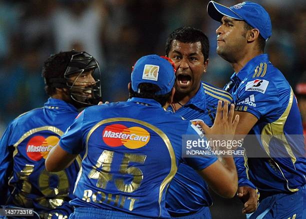 Mumbai Indians bowler Pragyan Ojha is congratulated by teammates after taking the wicket of unseen Pune Warriors India batsman Steve Smith during the...