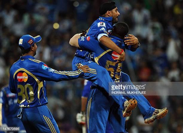 Mumbai Indians captain Harbhajan Singh and Pragyan Ojha celebrate with teammate Kieron Pollard after the dismissal of unseen Rajasthan Royals Amit...