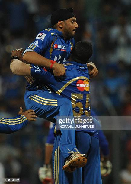 Mumbai Indians captain Harbhajan Singh celebrates with teammate Kieron Pollard after the dismissal of unseen Rajasthan Royals Amit Singh during the...