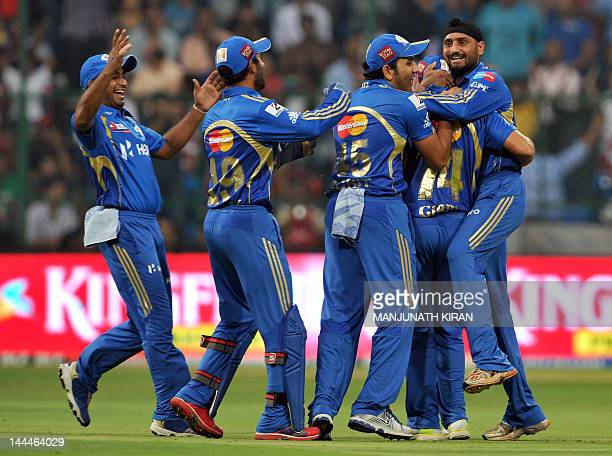 Mumbai Indians captain Harbhajan Singh celebrates with teammates the wicket of Royal Challengers Bangalore batsman Virat Kohli during the IPL...