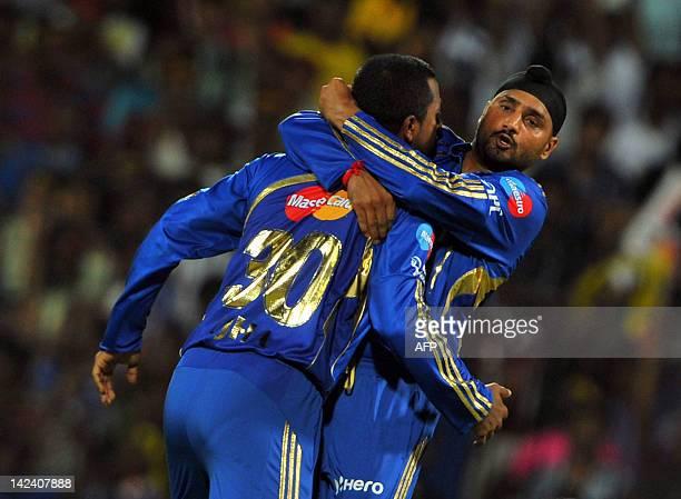 Mumbai Indians captain Harbhajan Singh jumps onto fielder Pragyan Ojha while celebrating the dismissal of unseen Chennai Super Kings batsman Dwayne...